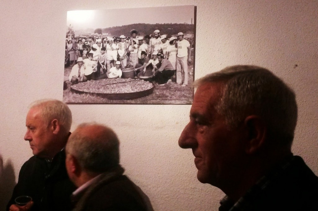 Una foto al fondo antigua y vecinos durante la celebración del aniversario