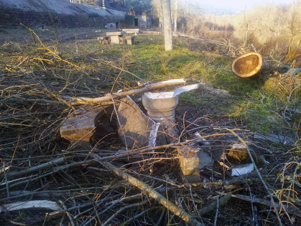 Un banco de merendero roto con ramas encima