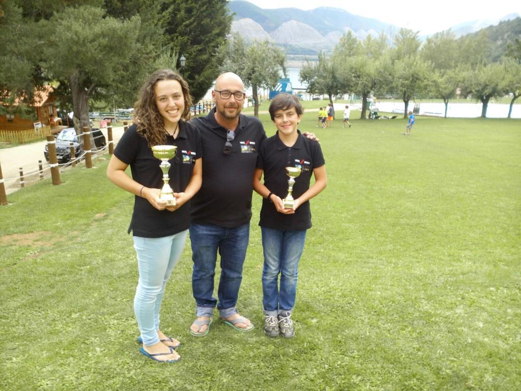 Leonor y Gonzalo recibiendo los trofeos y junto a su entrenador Raúl García.
