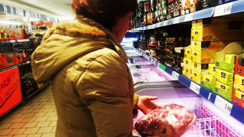 Una mujer mira con desconfianza la carne en un supermercado de O Barco