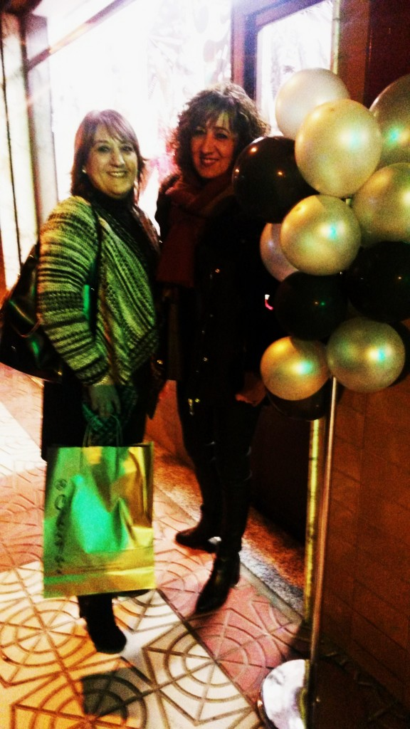 Con la bolsa de la compra junto a un negocio adornado con globos