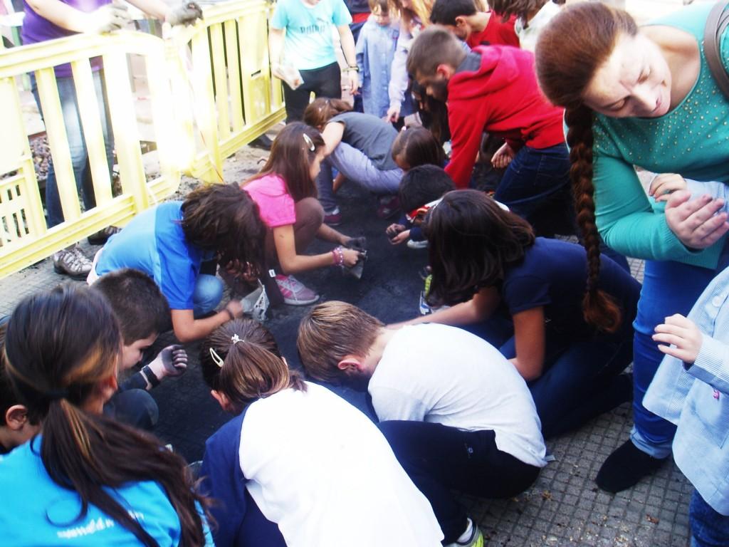 Los niños arremolinados sobre los restos de carboncillo