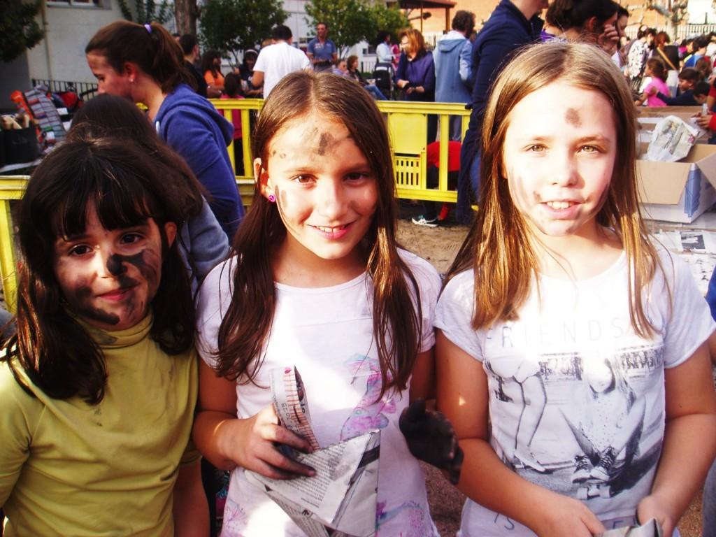 Tres simpáticas niñas con hollín en las manos y la cara