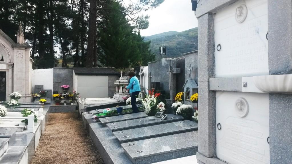 Una mujer subida a una tumba limpiando horas antes de la misa de Todos los Santos en O Barco