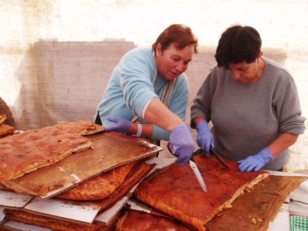 Dos mujeres de la organización cortando la empanada