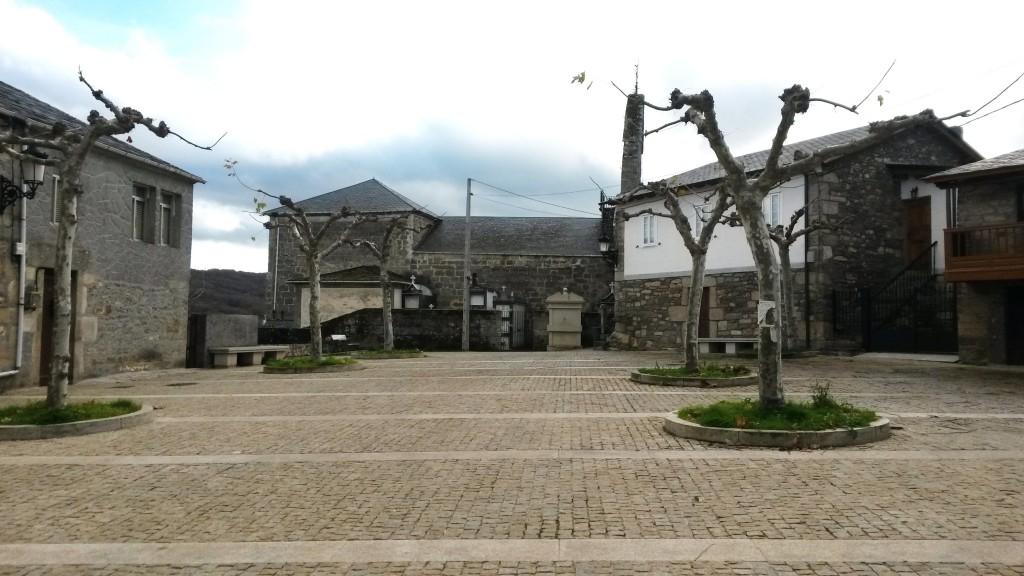 La fuente de la Plaza de O Bolo, al fondo, delante del cementerio y la iglesia
