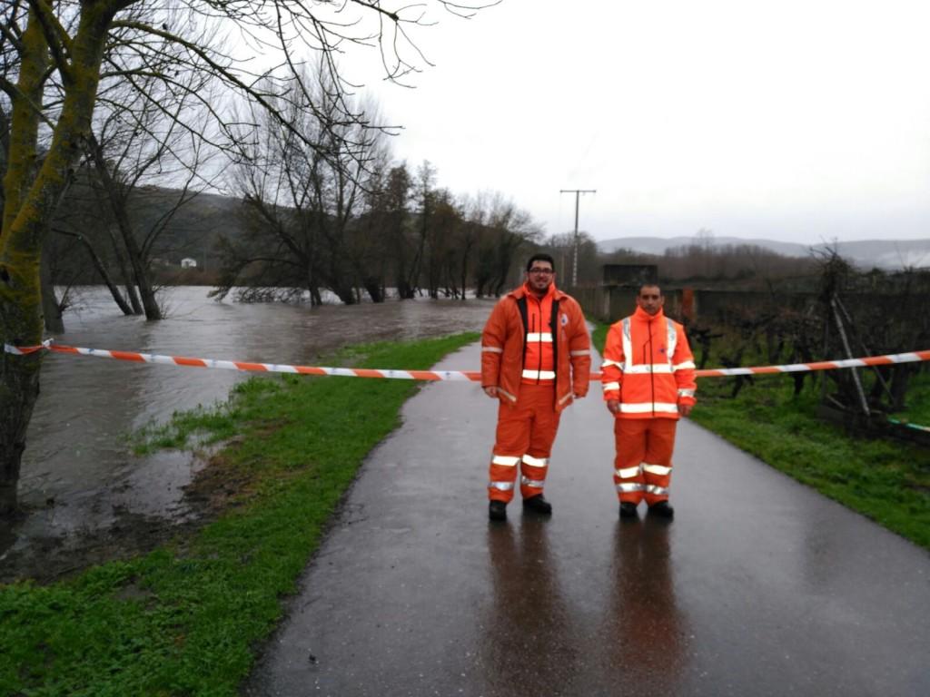 Dos operarios de Protección Civil de A Rúa junto al vial anegado por el Sil en A Rúa