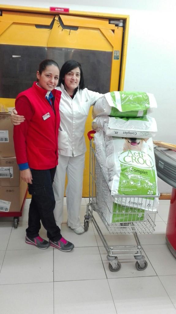 Trabajadoras del supermercado Familia entregando alimentos para los perros