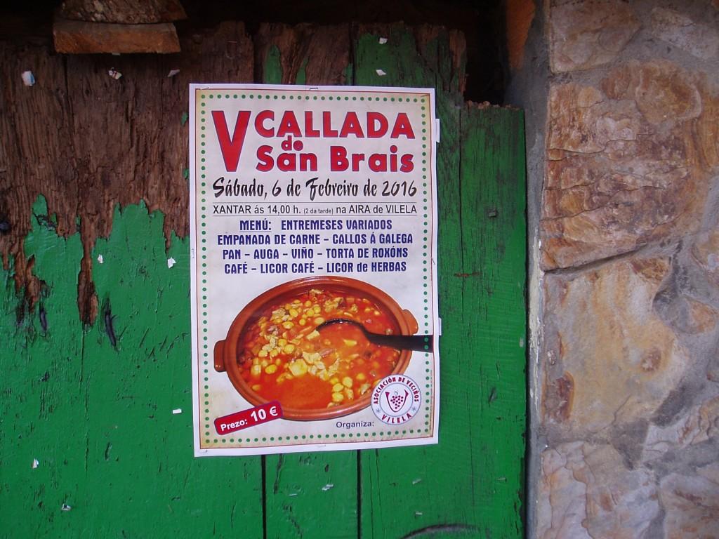 Cartel de la fiesta pegado en la puerta de una casa antigua de Vilela
