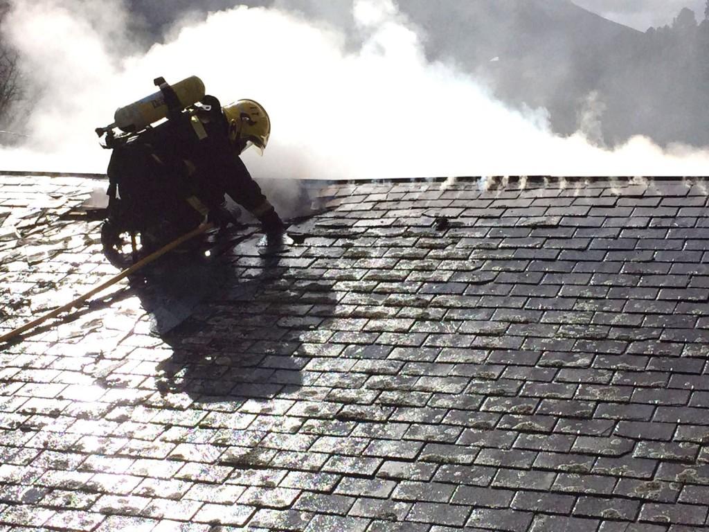 Un bombero en el tejado de la vivienda incendiada en O Mazo
