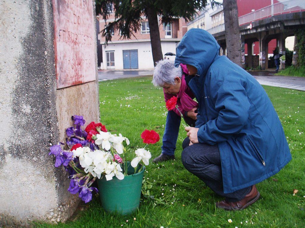 Con flores al pie de la escultura que recuerda a las víctimas del franquismo