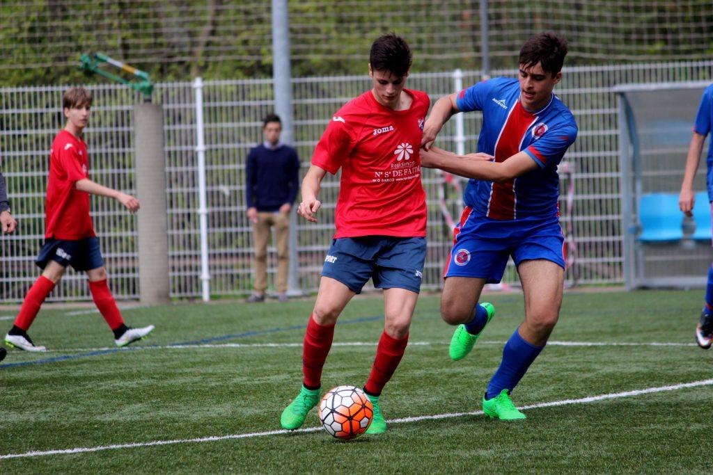 Juan del equipo cadete conduce el balón ante la presión de un jugador de la UD Ourense
