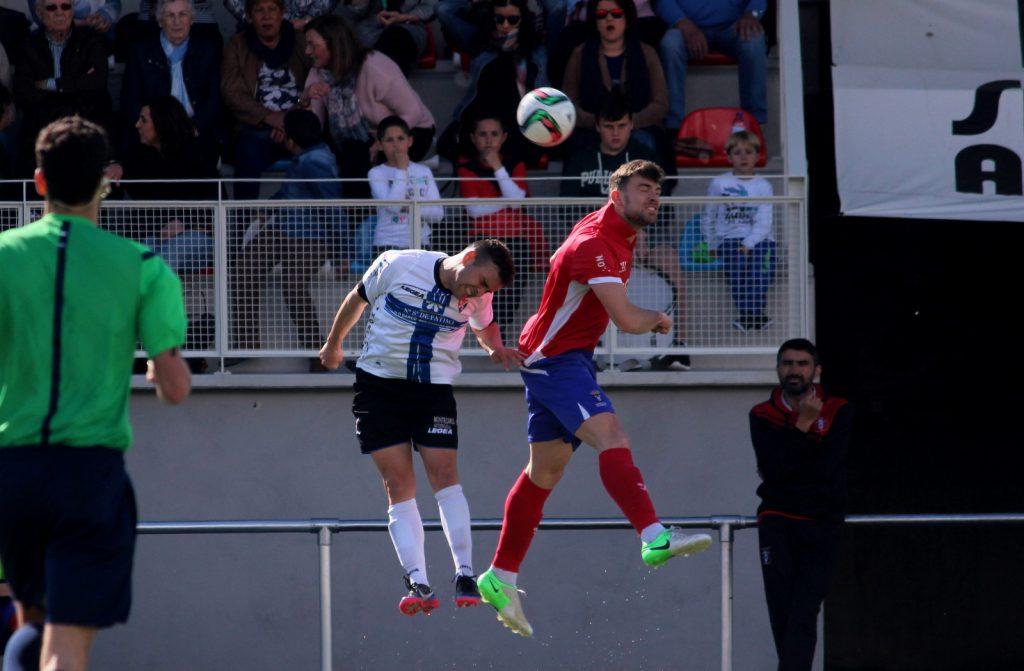 Diego Tato pugna un balón por alto ante la mirada de Marcos Montes