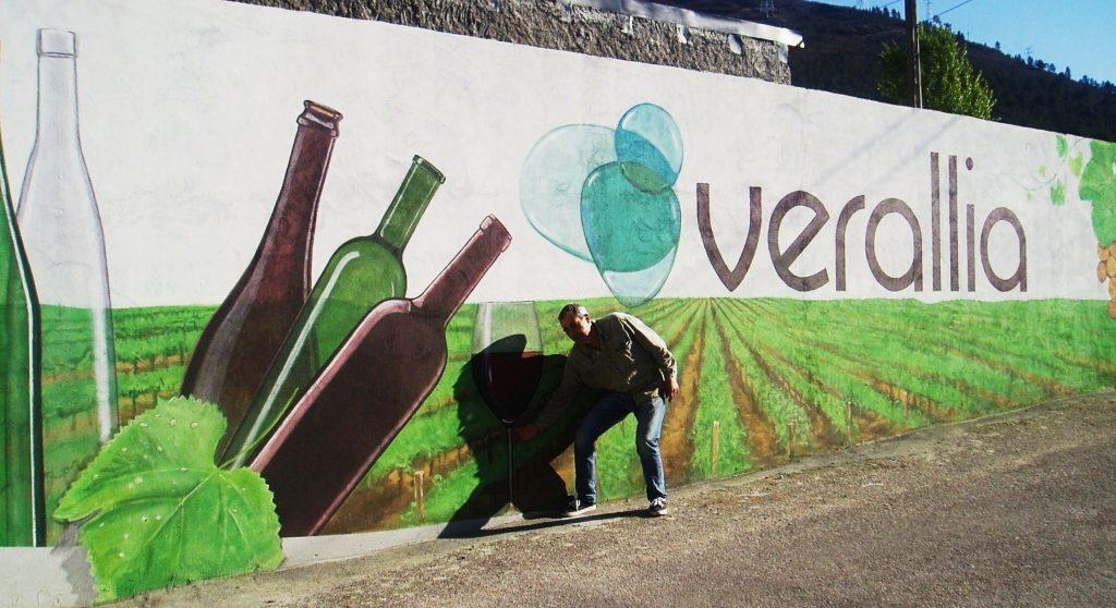 Lilí con uno de sus murales en la fachada de un local comercial