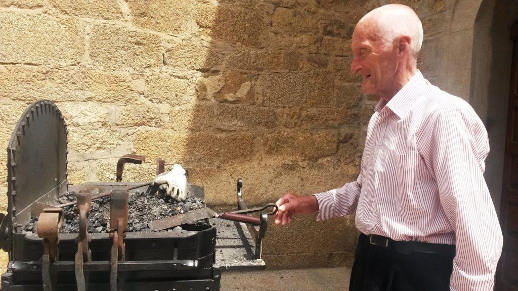 Salvador remueve carbón en un Fol de Fragua del artesano Ignacio Díaz en Petín