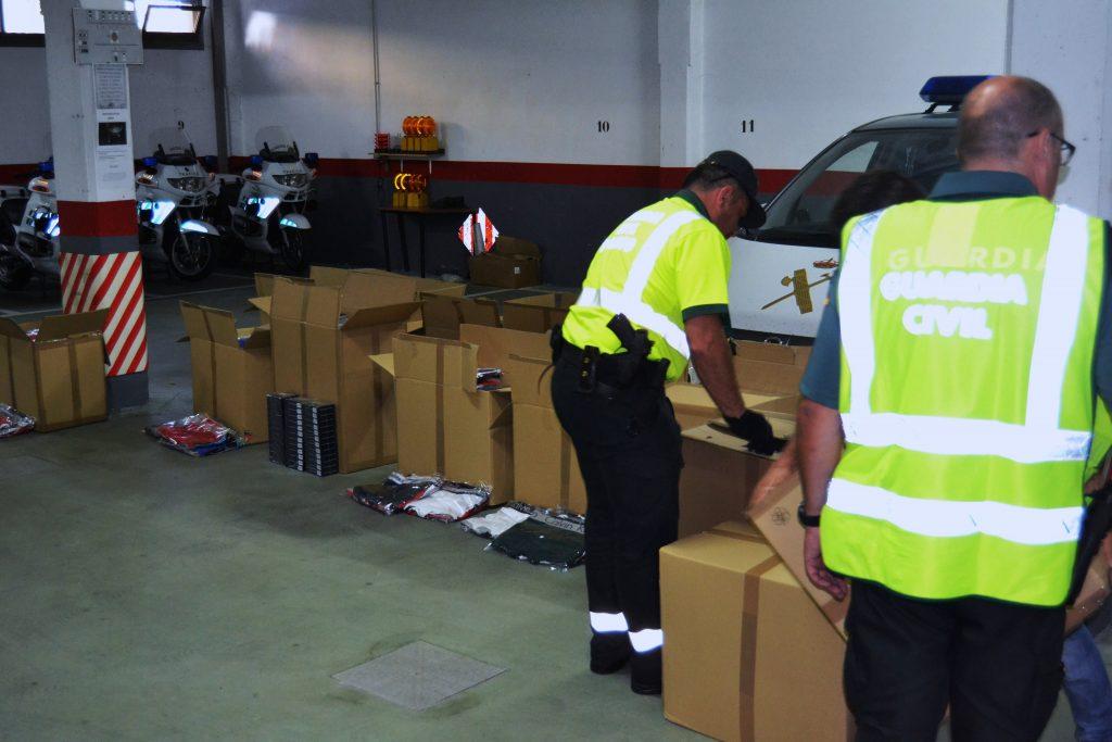 Agentes de la Guardia Civil abriendo cajas de ropa falsificada