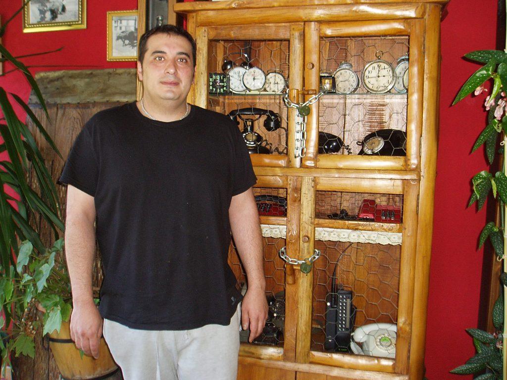 Nicolás González Ribalonga junto a la colección de relojes y teléfonos antiguos