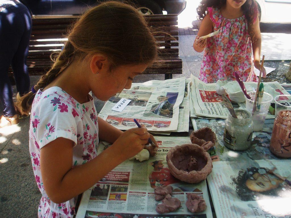 Una niña muy concentrada con su cuenco de cerámica