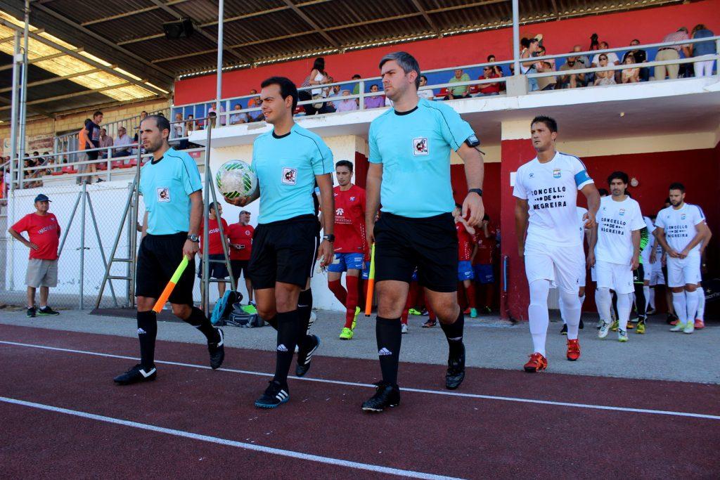 Trío arbitral y jugadores de ambos conjuntos saltando al césped de Calabagueiros
