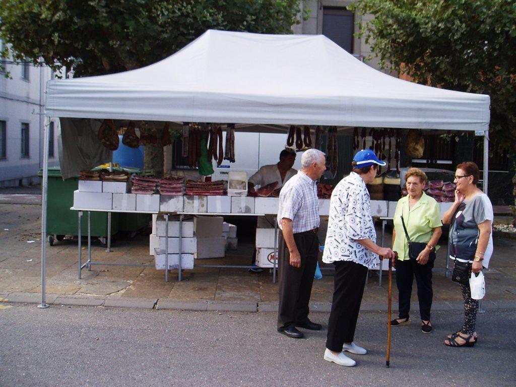 Vecinos de Vilamartín charlan después de comprar en la feria