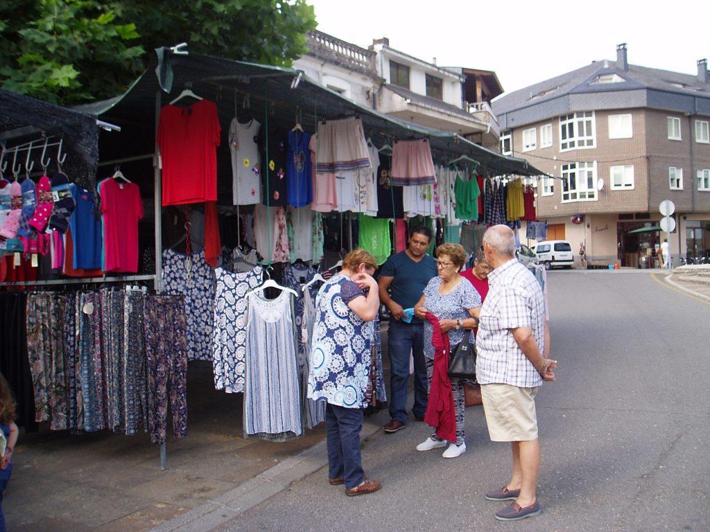 Vecinos de Vilamartín probándose ropa en un puesto de la feria