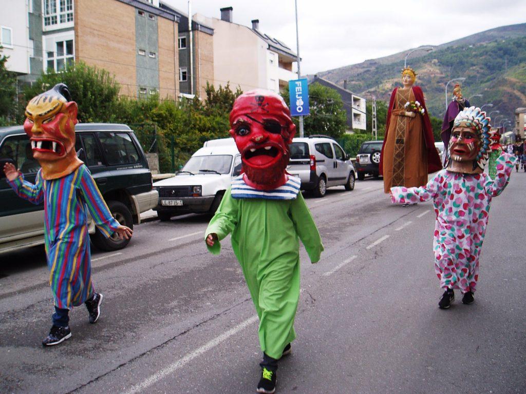 Cabezudos y calantornias desfilando por delante de la procesión