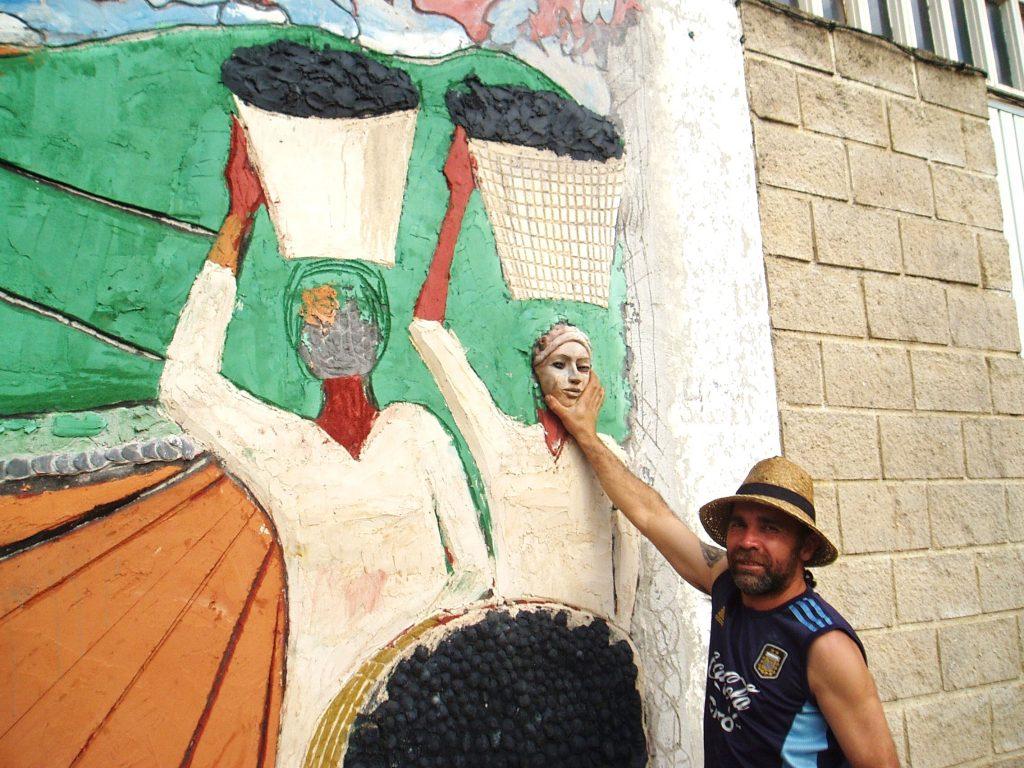 Leonardo Corazza prueba una de las caras de cerámica sobre el mural