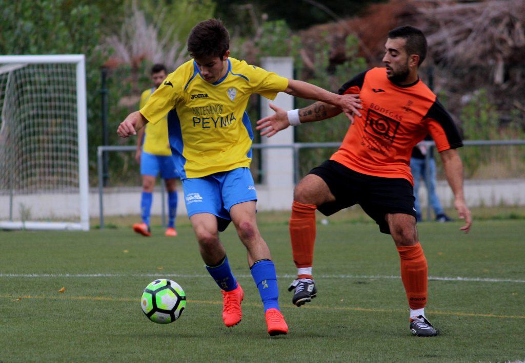 Alex Domínguez lucha por el balón con un jugador del Caldelao
