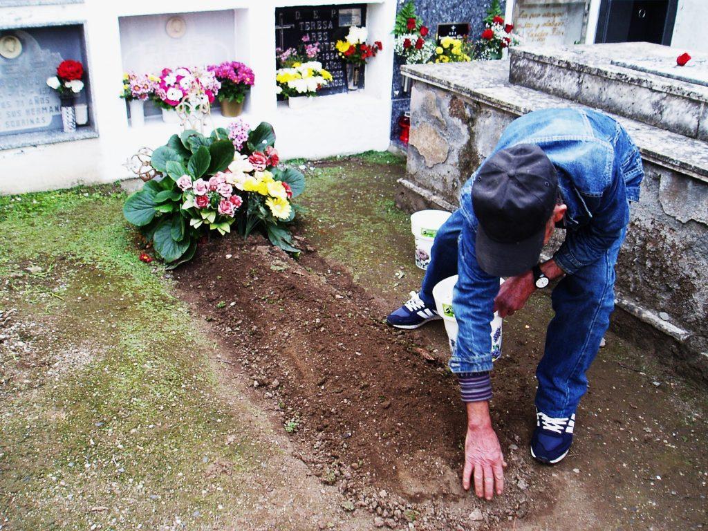 Acondicionando una tumba en tierra el día de santos en A Rúa Vella