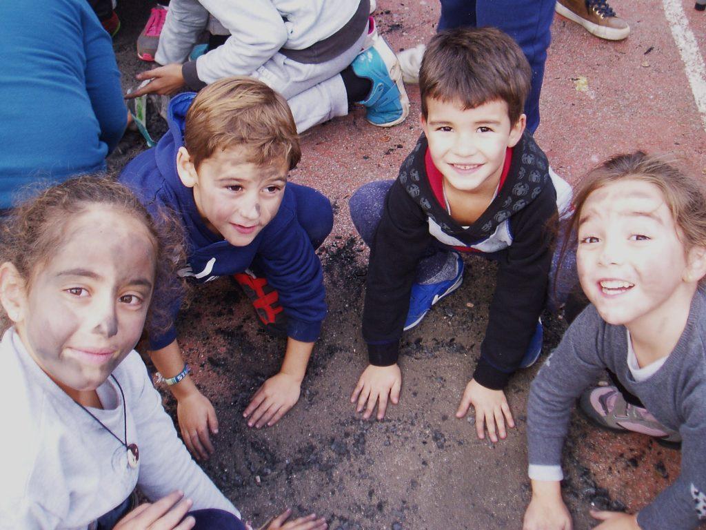 Cuatro niños en el suelo para pintarse con hollín