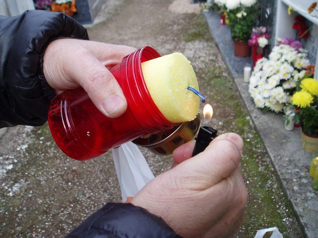 Encendiendo una vela para depositar a pie de tumba en A Rúa