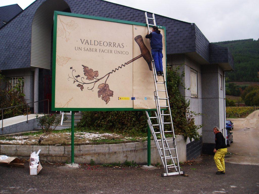 Operarios colocando a nova campaña gráfica no panel situado frente o edificio do Consello Regulador