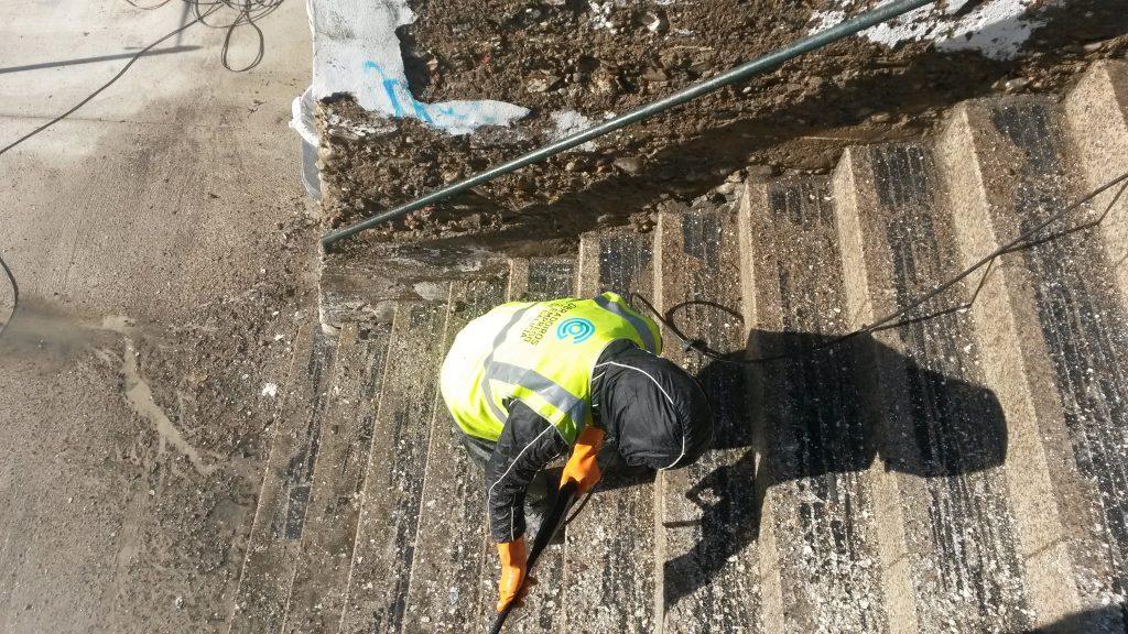 Un alumno limpia el muro de las escaleras de subida al paseo